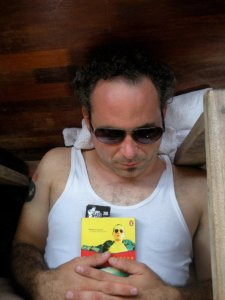 D.D. Miller snoozing on the floor of a boat that is cruising down the Mekong River in Laos. This is the pocketbook edition of Baroque-a-nova.
